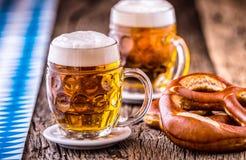 Beer. Oktoberfest.Two cold beers and pretzel. Draft beer. But draft. Golden beer. Golden however. Royalty Free Stock Photo