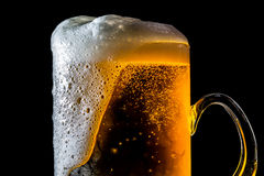 Beer overflowing large glass with foam and bubbles isolated Stock Photography