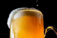 Beer overflowing large glass with foam and bubbles isolated Stock Photos
