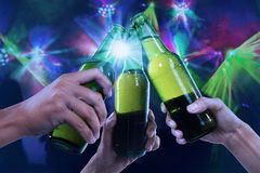 Beer party. Closeup of hands toasting with bottles of beer at the party club Stock Image