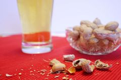 Beer and peanuts. On red doily.  Snack food and beverage Stock Photo