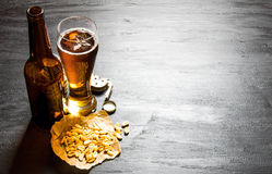 Beer with peanuts on the black wooden table. Free space for text. Royalty Free Stock Images