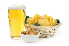 Beer, peanuts and crisps. Beer pint with peanuts bowl and basket of crisps royalty free stock photos