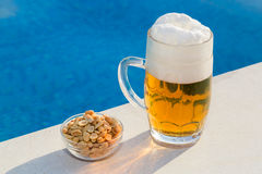 Beer and peanuts by the pool Royalty Free Stock Photography