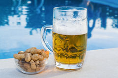 Beer and peanuts by the pool Stock Photography