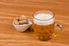 Beer and peanuts on table Royalty Free Stock Photography