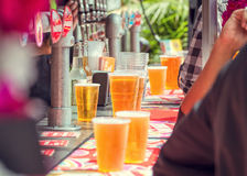 Beer and people at outdoor bar. Plastic cups of beer and cider at an outdoor bar in summer with people drinking royalty free stock image