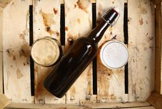 Beer percent. Bottle and full glasses of beer looking as a percent sign in a dirty wooden crate Stock Photos