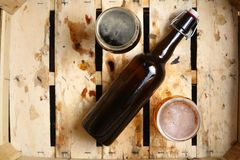 Beer percent. Bottle and full glasses of beer looking as a percent sign in a dirty wooden crate Stock Photography