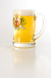 Beer Pint. Isolated mug of beer with froth reflecting on white glossy surface Royalty Free Stock Photo
