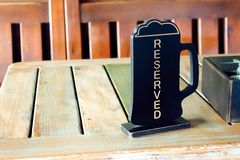 Beer pinta reserved sign on wooden table in pub, cafe, restaurant. Order lunch, dinner, breakfast in the pub royalty free stock photos