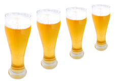 Beer pints in a row. With frothy heads isolated on white Stock Photography