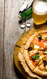 Beer and pizza on wooden table. Stock Photography