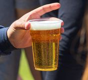 Beer in a plastic cup in hand. In nature stock images