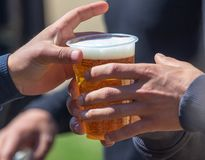 Beer in a plastic cup in hand. In nature stock photography