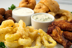 The beer plate with spicy chicken wings, calamari rings, fries onion rings, cheese balls, breaded, tartar sauce and garlic Stock Photography