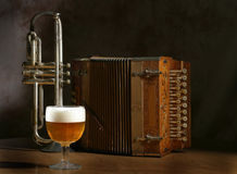 Beer and Polkas. Glass of beer with cornet and accordian in background Stock Photography