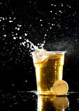 Beer pong game. Beer and ping pong balls over black royalty free stock images