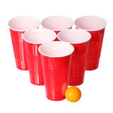Beer pong. Red plastic cups and orange ping-pong ball isolated on white. Closeup Royalty Free Stock Photo