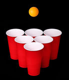 Beer pong. Red plastic cups and orange table tennise ball over black Royalty Free Stock Images