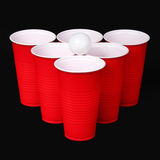 Beer pong. Red plastic cups and ping pong ball over black Royalty Free Stock Photography