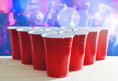 Beer pong tournament layout. Many red party cups in a nightclub full of people dancing on the dance floor in the background. Stock Photo