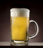 Beer pour. Beer glass with drops on wood bar Stock Images