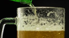 Beer is poured into a glass on a dark background. Beer is poured into a glass from a bottle on a dark background foam flows down a glass stock video