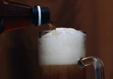 Beer poured into a glass with a nice foam. Beer poured into a glass with a bottle royalty free stock photo