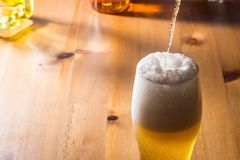 Beer is poured into a glass stock photos