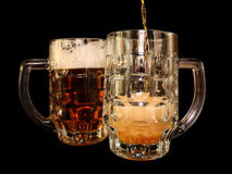 Beer is poured into a mug Stock Photos