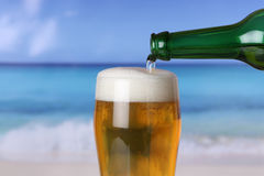 Beer pouring from bottle into glass on beach Stock Image