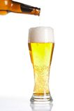Beer pouring from bottle into glass isolated. On white Royalty Free Stock Photos
