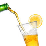 Beer pouring from bottle into glass with lemon Royalty Free Stock Photography