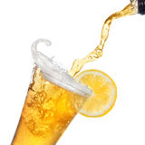 Beer pouring from bottle into glass with lemon Stock Photos