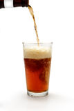 Beer pouring from bottle to Glass. Golden foaming Beer being poured into Beer glass on white background Stock Photos