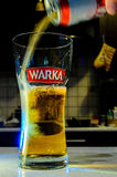 Beer pouring from can into glass on blurred kitchen. Picture shows pouring lager beer into glass on the blurred kitchen. Splashed beer creates interesting effect Royalty Free Stock Photo