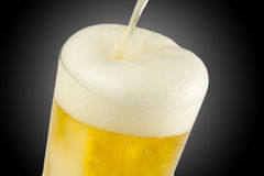 Beer Pouring In Glass. A full glass of beer being poured Royalty Free Stock Photos