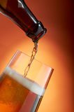 Beer pouring into the glass Stock Images
