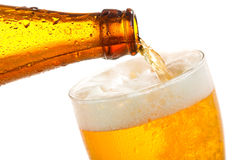Beer pouring into glass. On a white background Royalty Free Stock Image
