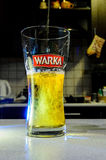 Beer pouring into glass on blurred kitchen. Picture shows pouring lager beer into glass on the blurred kitchen. Splashed beer creates interesting effect inside Stock Images