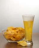 Beer pouring into glass and chips Stock Photos