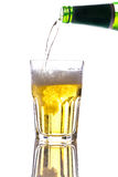 Beer pouring into glass. Isolated on white background. Green bottle with fresh and cold beer Royalty Free Stock Image