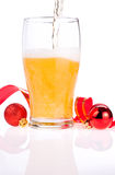 Beer pouring glass, Red ribbon and Christmas Balls Royalty Free Stock Images
