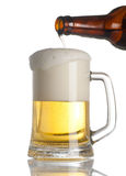 Beer pouring into glass on white Royalty Free Stock Image