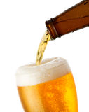 Beer is pouring into glass. On white background Stock Image