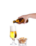 Beer pouring from green bottle into glass and crackers  isolated Stock Image