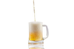 Beer pouring into half full glass  over white background Stock Images