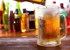 Beer pouring into mug stock photography