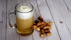 Beer pouring into mug and peanuts stock footage
